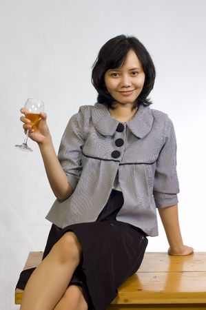Young beautiful asian business woman celebrating her success with wine and sit on the table Stock Photo - 5675680