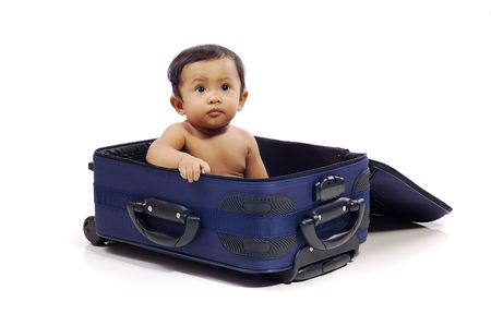Baby girl in the blue suitcase on white background. Ready to travel
