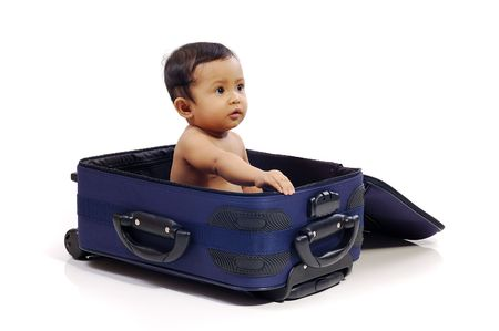 Baby girl in the blue suitcase on white background. Ready to travel photo