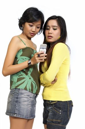 Two pretty asian girls reading bad news SMS on mobile phone. Isolated on white background Stock Photo - 6036931