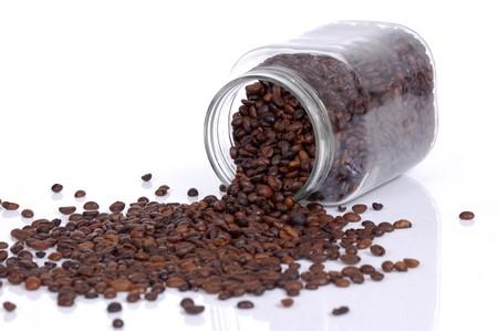 frasco: Los granos de caf� dentro de vidrio jar gota sobre fondo blanco  Foto de archivo