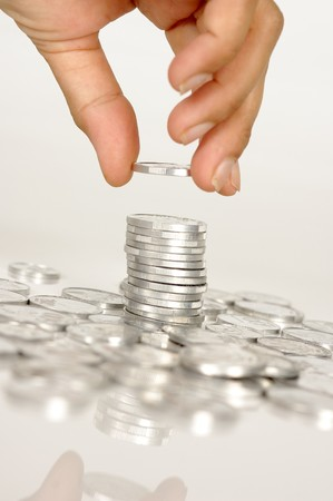 Human hand hold a coin on pile of coins Stock Photo