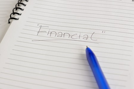 Financial words been write with blue pen on notebook photo