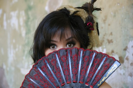 Chinese woman wearing victorian costume holding a fan, shoot at grunge building photo