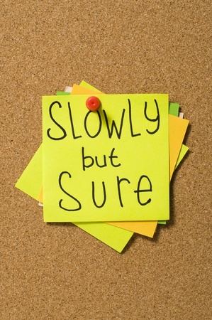 Slowly but sure writes on the paper over cork board Stock Photo - 10313099