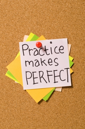 practise: Practice Makes Perfect write on the paper on the cork board Stock Photo