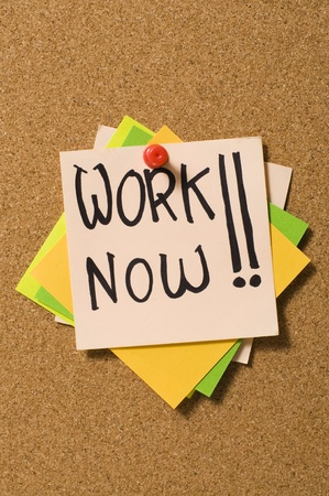 Work Now writes on the paper on the cork board Stock Photo - 10313093