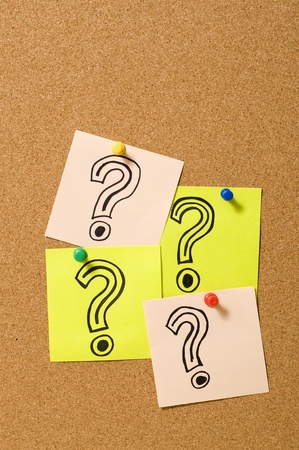 Question Marks writing on the paper attached on cork board Stock Photo - 10313104