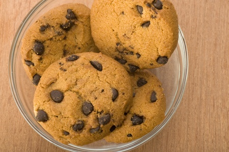 choco chips: Chocolate chip cookies in glass bowl over wooden background