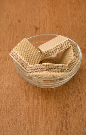 Chocolate wafer in the glass bowl. Shot on wooden background photo