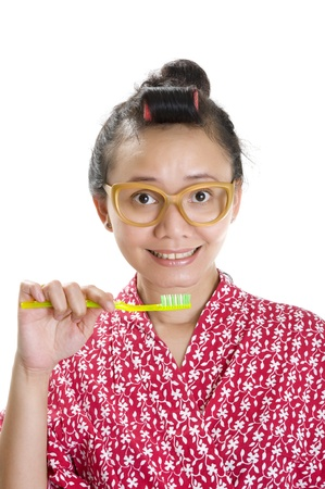 Woman with hair roll and glasses brush her teeth isolated over white background photo