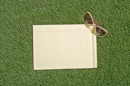 Blank paper note on the green grass outdoor photo