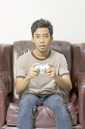 Young male playing video game on the couch on living room photo