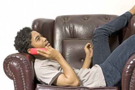 Man calling someone and sitting on the brown couch photo