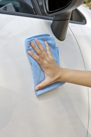 Woman cleaning her new car using microfiber cloth photo
