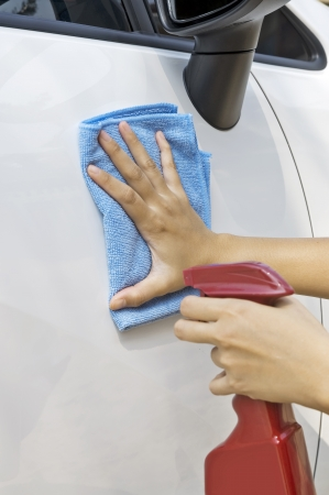 Woman waxing her new car using spray wax photo