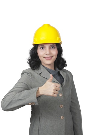 Woman in yellow hat show her thumb isolated over white background photo