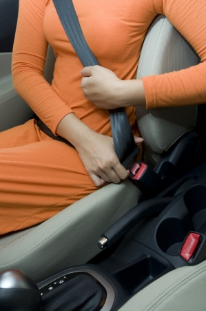 Woman sit on car seat and fasten safety belt photo
