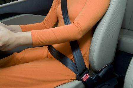 cinturon seguridad: Mujer sentada en el asiento del coche y sujetar el cintur�n de seguridad Foto de archivo