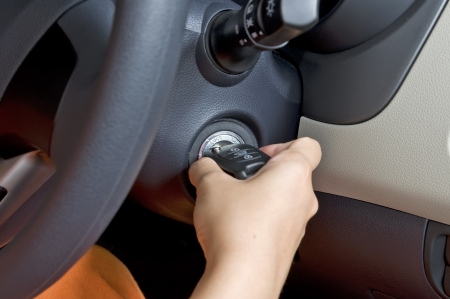 Woman hand hold car key ready to start engine photo