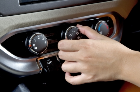 hands in the air: Woman hand controlling heat on her car Stock Photo