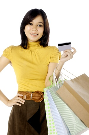 Woman holding credit card ready for shopping. Isolated over white background photo