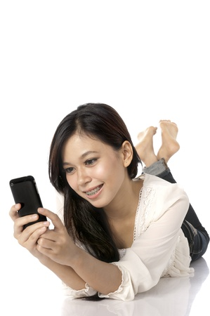 Asian woman lay on the floor while texting her friend photo