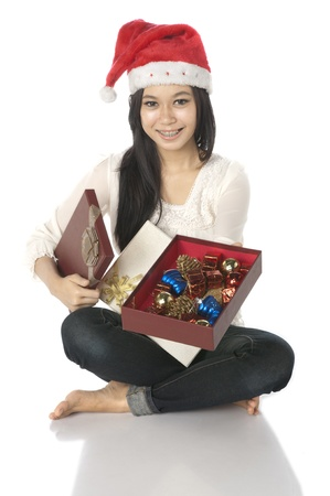 Woman wearing santa hat hold gift box isolated over white background photo