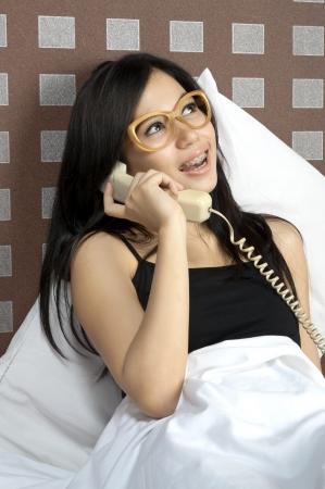 Woman make a call while in bed before sleep photo