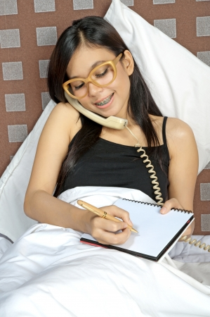 Asian woman call and write while in bed photo