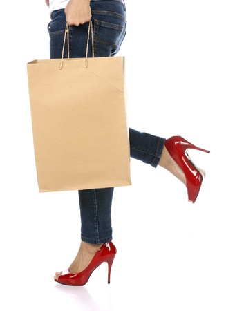 Shopping bag, jeans, and high heels closeup with copy space on shopping bag  Shopping woman profile close up isolated on white background, photo