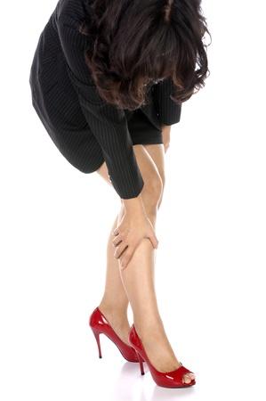 tacones rojos: Mujer de negocios que tiene las piernas heridas por uso de tacones altos