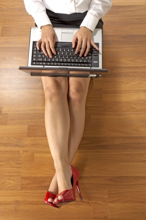 Above view of businesswoman typing on laptop with stretched legs photo
