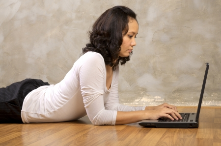 Woman lying on the wooden floor using laptop notebook Stock Photo - 14283295