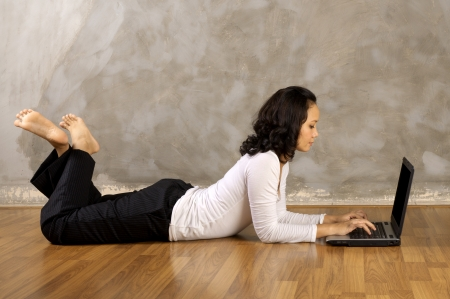 Woman lying on the wooden floor using laptop notebook photo