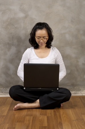 Asian woman typing with laptop notebook on the wooden floor photo