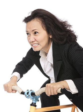 Business woman riding bicycle isolated over white background photo