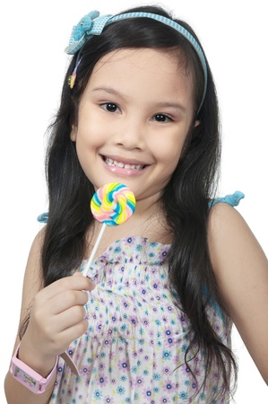 Mix race asian caucasian girl eating lollipop isolated over white background photo