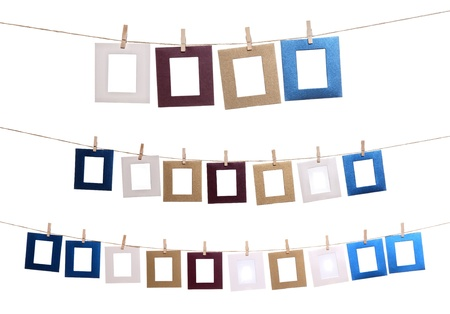 Collection of blank photo frames hanging by clothespins on a rope.  photo
