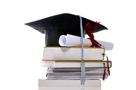 Tapa de graduación, libros y desplazamiento aislado sobre fondo blanco.