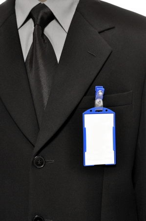 nametag: A businessman wearing a blank name tag and a sharp business suit.
