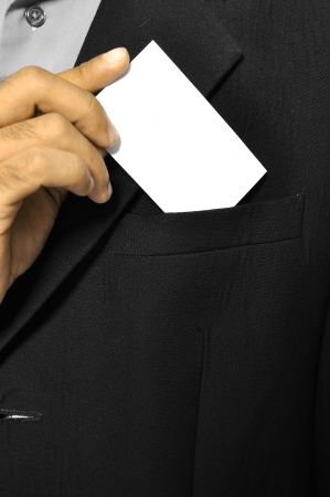 Business man putting a blank business card in his suit pocket photo