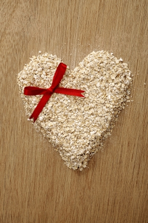 Heart shape oatmeal on wooden background. Good for healty food concept photo