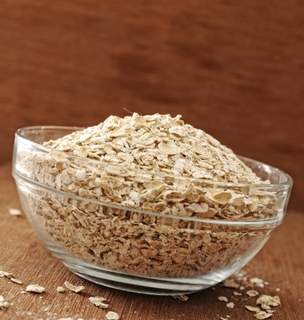 Oatmeal in glass bowl. Shot with wooden background photo