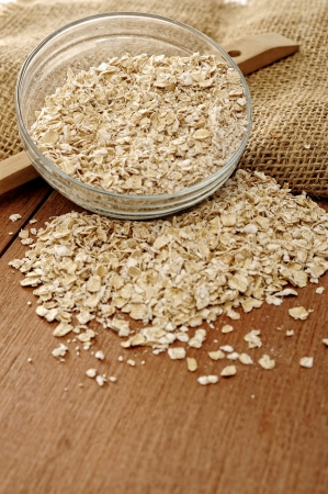 Oatmeal in glass bowl. Shot with wooden background and burlap photo