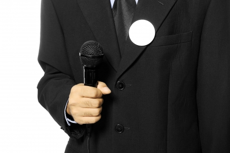 Man with black business suit with blank pinned button hold microphone  You can put your design on the button  Election day background or concept Stock Photo - 15717838