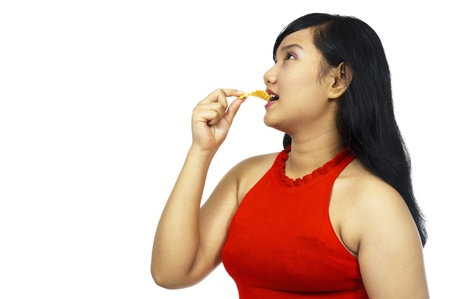 Fat asian chubby girl eating snack isolated over white background photo