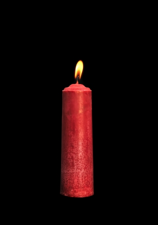A single burning red candle isolated in front of black background photo