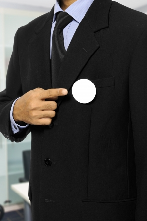 Man with black business suit with blank pinned button. You can put your design on the button. Election day background or concept Stock Photo - 18178016