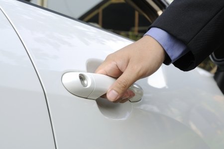 Chauffeur or driver hand opening white car door Stock Photo